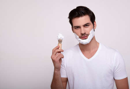 Beautiful well-groomed young macho man with shaving foam on his face, dark volsos, in a white T-shirt stands on a white background and holds in his hand a shaving anoint. Copy space.