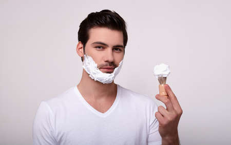 Enjoying the morning routine. Handsome young man applying shaving cream and looking at camera while standing against gray background. The concept of men's hygiene and beauty of the face, body.