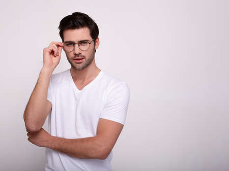 Pensive Caucasian man in glasses and white t-shirt isolated on grey studio background look at blank copy space aside thinking, thoughtful guy in spectacles pondering consider sale offer. Copy space.