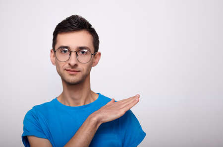 Young stylish, fashionable young guy with trendy haircut in round glasses for vision and a blue T-shirt stands straight, looks into the frame, hand casually swipes dust from the shoulder. Copy space.