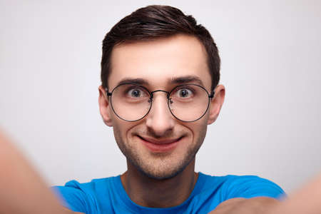 Close-up, surprised by the joyous cheerful face of a young white man with brown hair and green eyes, wearing blue T-shirt glasses. A young man takes a selfie in the studio against a white background. Stock Photo