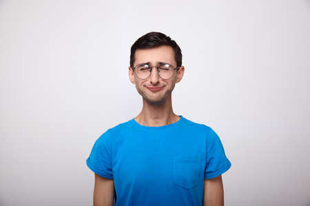 A thin, sophisticated, sad young white man in a blue T-shirt and eyes, standing upright, closed his eyes and whets his mouth. Emotion of sadness, depression, pessimism in teenagers, millennials. Stock fotó