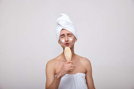 Romantic brooding white young man after the shower, in a white towel, holds in his hand a comb and closes his eyes sings. The concept of spa, male beauty, mens morning routine. Copy space.