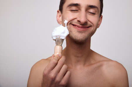 Cheerful happy happy young man holds in his hand a shaving anoint, dreamily closed his eyes, anticipating the morning procedure to care for his body.