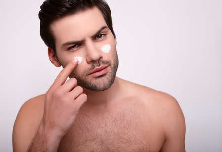 Close-up, a young serious handsome Caucasian man with dark hair, shirtless, applies finger cream on his face. The concept of skin care, beauty, skin hydration, men's hygiene and beauty.