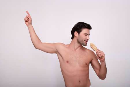 Romantic brooding white young man after the shower, holds in his hand a comb and closes his eyes sings. The concept of spa, male beauty, mens morning routine. Copy space.