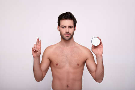 Attractive man puts cosmetic cream on his face, has healthy skin, looks straight, stands half-naked over a white studio wall, carries out facial procedures, posing at home in the bathroom. Copy space.