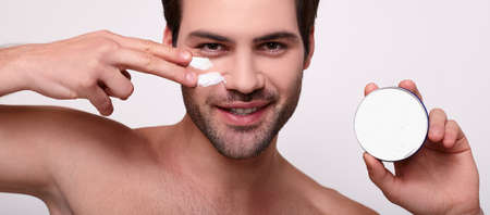 Close-up portrait of smiling shirtless young man applying facial cream, isolated on gray background. Skin care concept. Stock Photo
