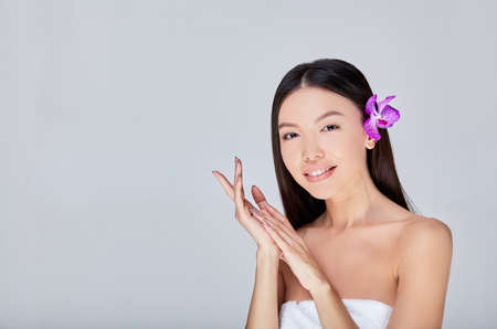 Portrait of a cheerful cute young naked Asian lady folded her arms near her face and holds a purple flower behind her ear, looking to the side playfully. Isolated with copy space on the left.