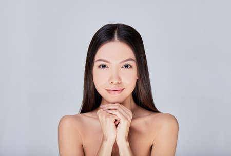 Central shot, image of cute asian girl with brown eyes and both hands under her chin. Women stands on background and looks straight. Copy space. Perfect young skin.