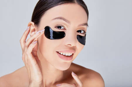Cosmetic mask for the skin under the eyes. False eye mask on an Asian girl with perfect healthy skin.