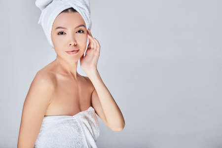 Closeup of a young beautiful Asian woman with perfect skin, in a white towel on her head, touching her silky facial skin, spa skin care procedures.