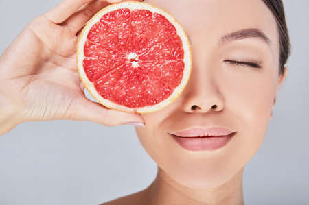 Close-up portrait of a young beautiful Asian woman with perfect skin, dreamily closed her eyes, holds a grapefruit near her face. Photo on a gray background. The concept of cosmetics with vmitamine C.