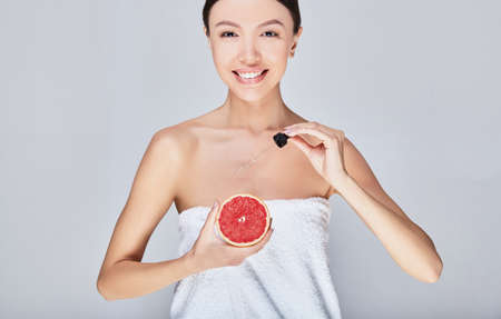 Clseup head shot of woman holding orange fruit. Beautiful young Asian woman with perfect skin is applying body oil with grapefruit extract. Cosmetics with Vitamin C. Imagens