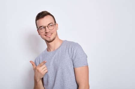 Young smiling man in a gray basic t-shirt with round glasses for vision, looks to the side, to the right, copy space for advertising isolated on a white background.