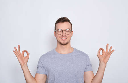 Concentrated nice calm man in a gray T-shirt standing with his eyes closed, relaxing during meditation, trying to find balance and harmony. Yoga and meditation concept.