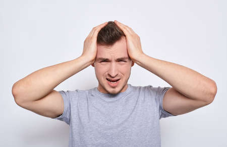 Close-up of a young man isolated on a white background in a gray casual t-shirt, touching his temples with his palms, as if suffering from a severe headache, clutching his head with his hands.