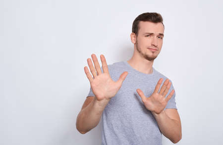 A young handsome white guy in a gray basic T-shirt, stretched his arms forward, shows his hands stop, does not want. The sad man says timeout, stop, shows reluctance. Фото со стока