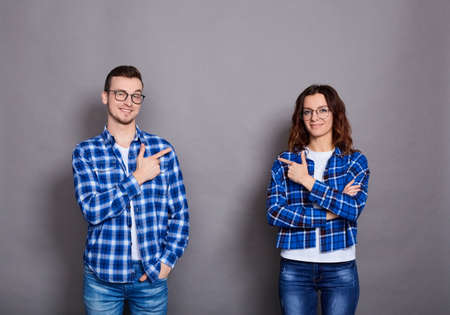 The young happy couple in white T-shirts, blue plaid shirts, glasses, stand on a gray background, and point their finger at each other, look straight and smile.
