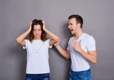 Couple of young woman and man with mustaches in white t-shirts and blue jeans. Enmity standing isolated over blue background. The concept of a crisis of relations.