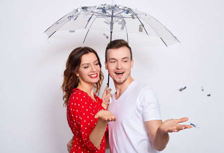 Portert, beautiful young happy couple in love together, laughing, couple hiding under an umbrella from falling confetti, hugging, catching confetti with their hands isolated on a white background.