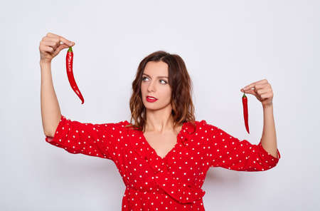 Beautiful young sexy Caucasian girl in a red dress, with bright evening make-up, holds in his hands a small and large chili pepper, compares size, chooses, poses on a white background. 免版税图像