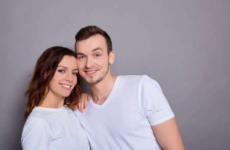 Portrait of a Caucasian lovely couple - a man with blue eyes hugs his charming, sweet woman, and they both look at the camera, standing against a gray background. Copy space.