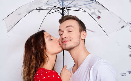 Kissing young cute tender Caucasian couple in love in fashionable elegant clothes with an umbrella under falling silver confetti isolated on a white background.