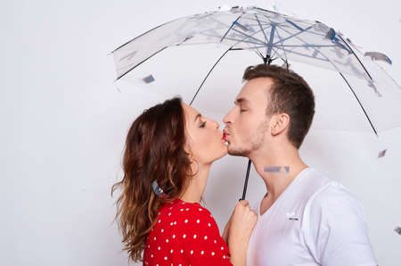 Kissing young cute tender couple in love in fashionable elegant clothes with an umbrella under falling silver confetti isolated on a white background.