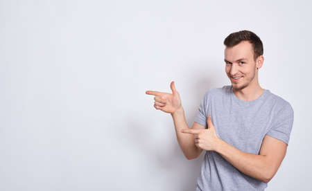 Closeup, young handsome athletic white man in a gray t-shirt, smiling, looking straight, pointing fingers to the left, isolated on a white background with copy space for your text. Copy space.