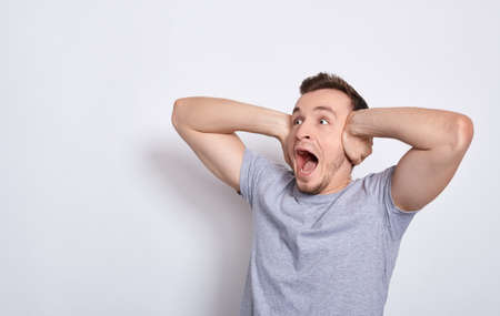 A young screaming angry man in a basic gray T-shirt, screaming noisily at the noisy neighbors from above, covering his ears with both hands, does not want to hear bad news. Copy space.