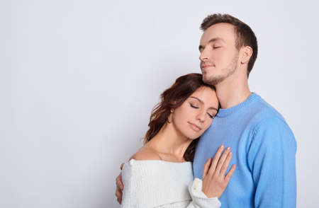Image of a tender attractive millennial couple in love closed their eyes, romantic relationship, young wife and family spouse, concept image of love and dating. Copy space.