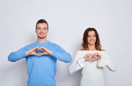 Funny happy young Caucasian lovers in light fashionable clothes, stand next to each other, show their hands heart, are in love, test emotions, smile on a white background.