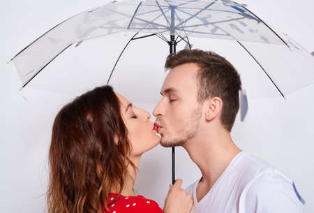 Portert, beautiful young happy couple in love together, laughing, couple hiding under an umbrella from falling confetti, hugging, guy kisses his girlfriend isolated on a white background.