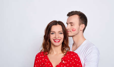 Charming couple in love, he, she, together forever, kisses her on the cheek, joyful and cheerful, a girl in red and a guy with a kiss on the cheek.