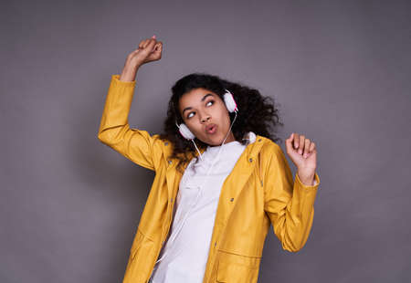 A cheerful young dark-skinned girl, in a white T-shirt and a yellow jacket, with magnificent curly hair, listens to music on headphones, sings, dances with her favorite music, looks to the side.