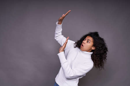 Frightened, troubled young Afro woman, in a white sweater, with curly curly hair, raised her hands up, something falls on her, she defends herself. On the left is the place to advertise your product.