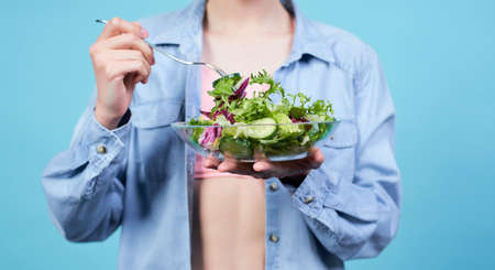 Cropped frame, young white slim girl, in a beige top and denim shirt, holding a bowl with a green salad and a fork in her hands. The concept of sports and diet. The concept of vegetarianism. Banque d'images
