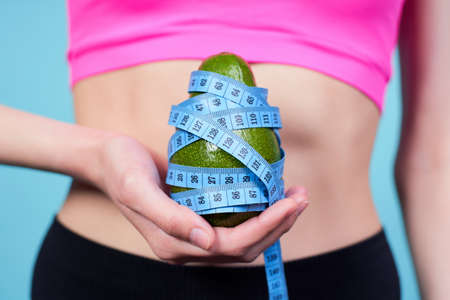Cropped shot, close-up of a sporty young girl, in a pink top, holding an avocado in her hand wrapped in a blue measuring tape, standing on a blue background. The concept of a keto and healthy fats.