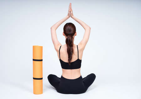A young healthy athletic flexible Caucasian girl, in a black top and leggings, practicing yoga and meditation, sits in a yoga pose, turning her back, an orange yoga mat is standing nearby.