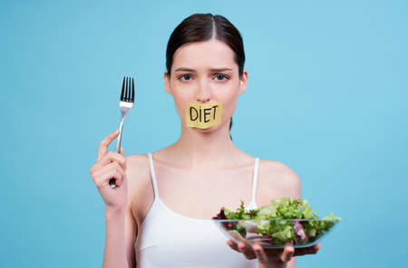A hungry sad young girl in a white top, holds in her hand a fork with a slice of cucumber and a bowl with green fresh salad, her mouth is sealed with a ribbon with the word food, she is losing weight.