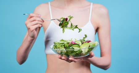Cropped picture, a young thin Caucasian girl, in a white top, holds a fork and a bowl with a fresh green salad, she eats properly, loses weight, stands on a blue background. Banque d'images