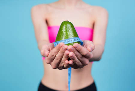 Cropped frame, a young white girl, in a pink top, holds an avocado in her hands, wrapped in a blue measuring tape, stands on a blue background. The concept of diet and sport.