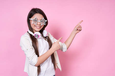 Cute funny stylish emotional Caucasian schoolgirl,smiles, rejoices to have fun, in stylish white glasses and points fingers to the right,in white jacket and headphones on pink background. Copy space. 写真素材