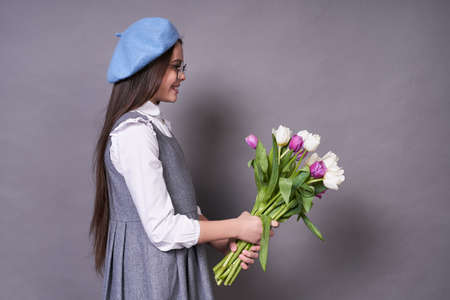 Young cute emotional child in glasses, holding multi-colored tulips in her hands and looking at them, happy with a gift to the left of the copy space, very joyful and surprised, on a gray background.