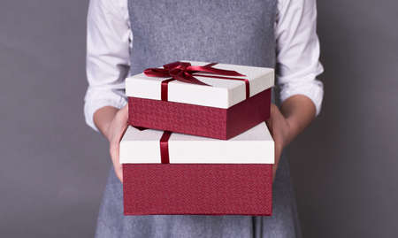 Portrait of a red-white cute gift box, which is gently and gently held by the hands of a child who gives or receives a long-awaited surprise, in a white sweater on a gray background. Copy space.