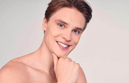 Surprised, shocked young naked man, a young man, blond with blue eyes, wears patches on his face to moisturize the skin, shocked by the effect of rejuvenation.