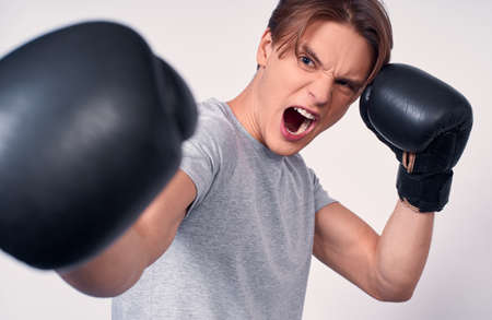 A young aggressive boxer, holding his hands in black boxing gloves near his face, emotion aggression. Caucasian young man boxing, shouting, sports, victory, adrenaline on a white background.