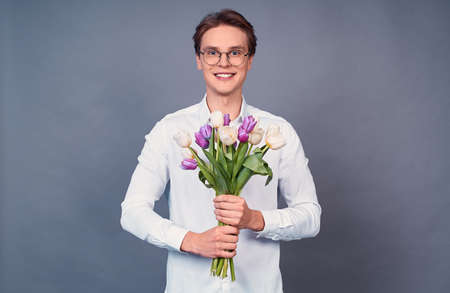 guy with a spoiled hairstyle, in a white shirt, holds broken white and pink tulips, looks straight, regrets about a failed date, stands on a gray background.