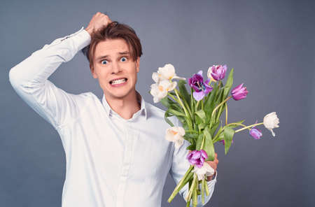 Sad scared guy with a spoiled hairstyle, in a white shirt, holds broken white and pink tulips, looks straight, regrets about a failed date, stands on a gray background. Фото со стока